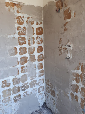 Shower wall with tiles pulled off and render, both old and new, showing.
