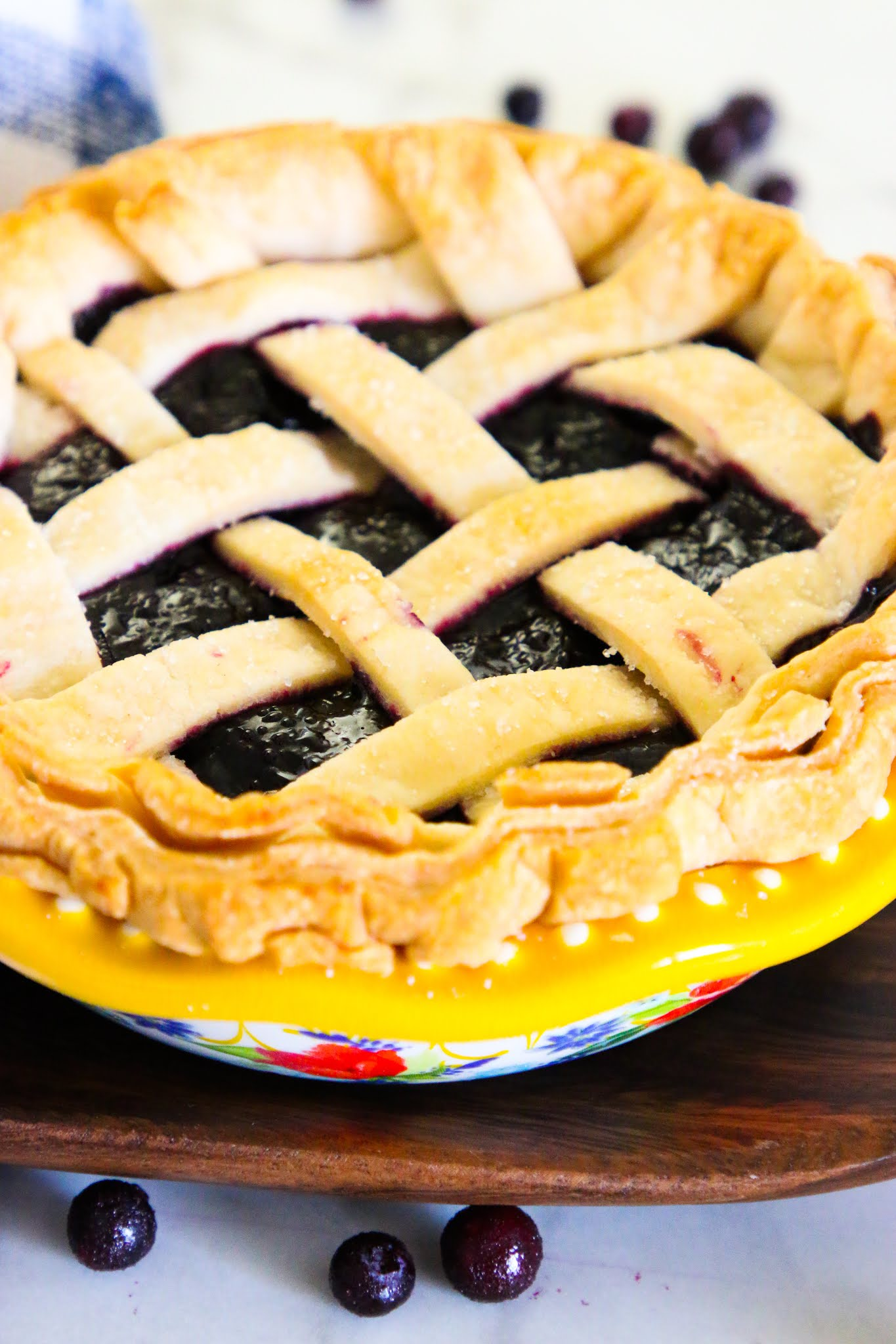 Blueberry pie in a blue pie plate with a blue dish towel in the background and blueberries scattered on the table.