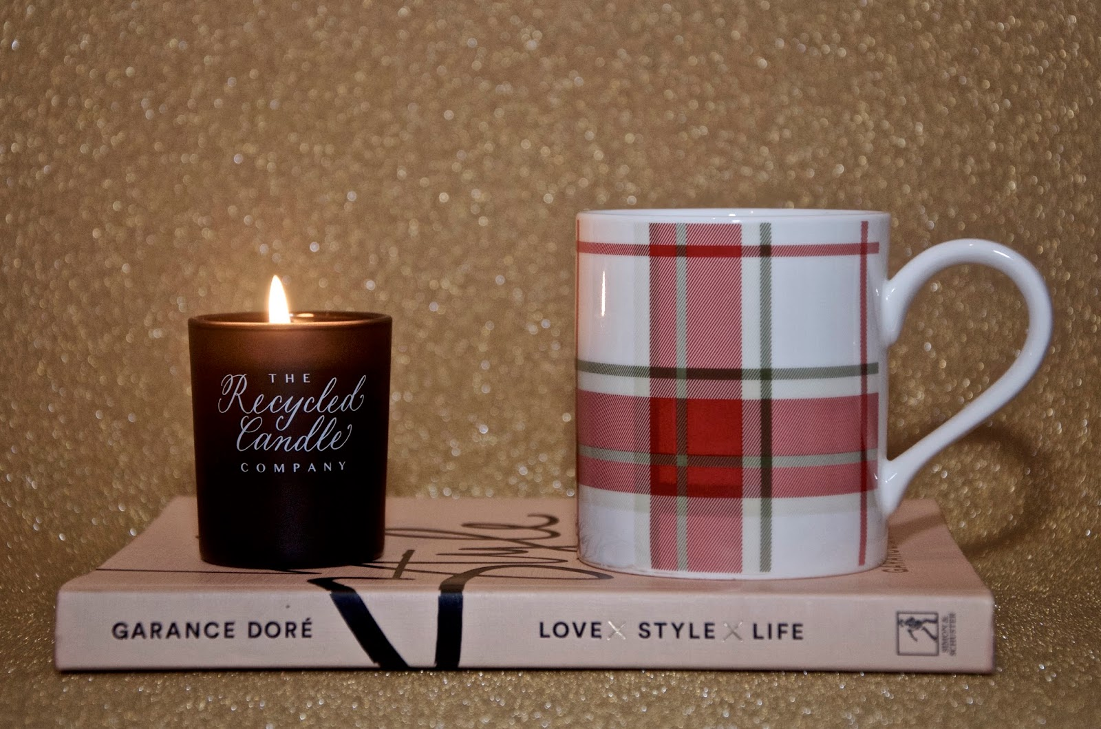 Black votive candle, pink book and red & green plaid Christmas mug