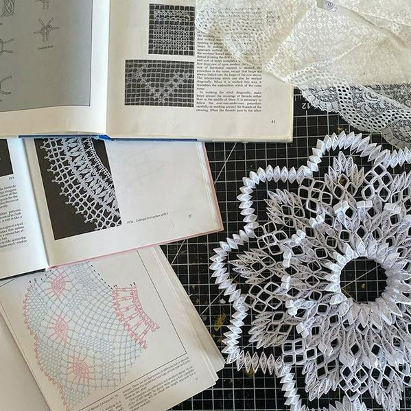 antique lace-making books open on work table next to quilled paper doily