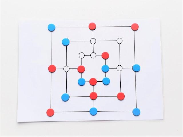 na zdjęciu plansza do gry w młynek z 24 polami połączonymi ze sobą liniami, na planszy piony w kolorach niebieskim i czerwonym ustawione w przypadkowy sposób