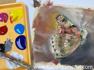 a paint tray next to a painting of a butterfly