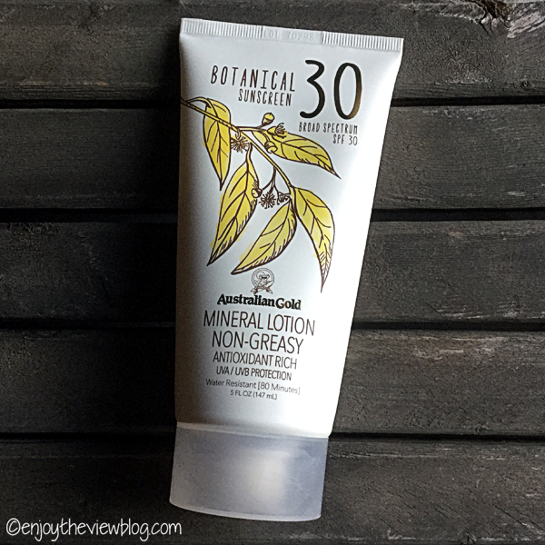 Tube of Australian Gold Botanical Mineral Lotion SPF 30 lying on a wooden table