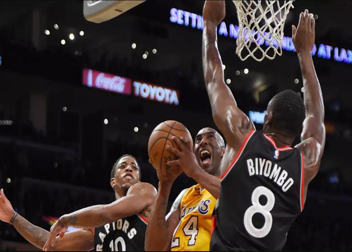 Pemain Los Angeles Lakers, Kobe Bryant sedang berusaha memasukan bola dari penjaga dua pemain Toronto Raptors DeMar DeRozan dan Bismack Biyombo selama pertandingan NBA di Los Angeles Pada 20 November 2015.