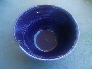 "A wide pottery bowl with a ""j"" cut into one side. The bowl is glazed in a deep purple glaze."