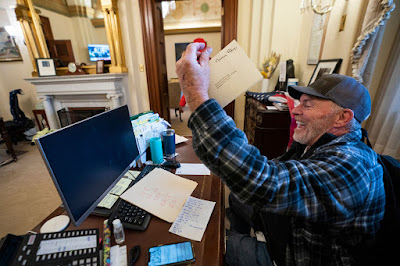 Richard Barnett sits at Nancy Pelosi's desk and gleefully holds up a letter.