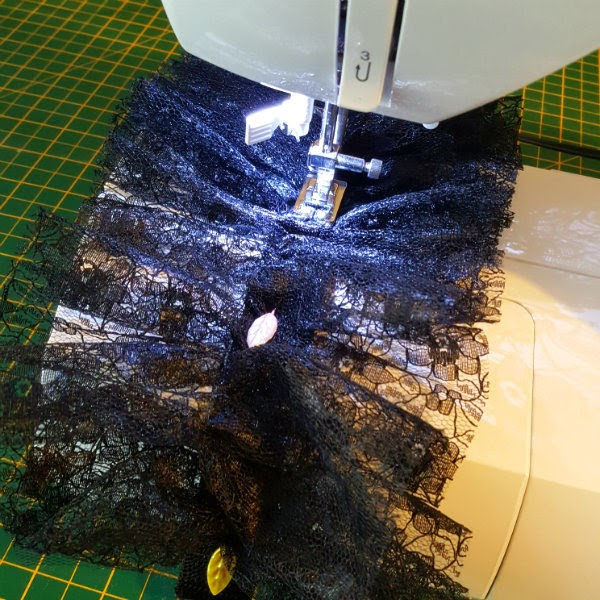 black lace fabric being sewn on a machine