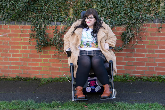 Plus size woman sat in wheelchair wearing brown mini skirt, black tights, Wizard of Oz t-shirt and cream teddy coat