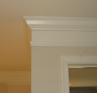 Crown molding given the illusion of built up or upgraded with extra molding and painting wall in between.