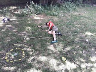 Alec pretending to ride an image of a bike made from sticks and leaves in the style of Andy Goldsworthy