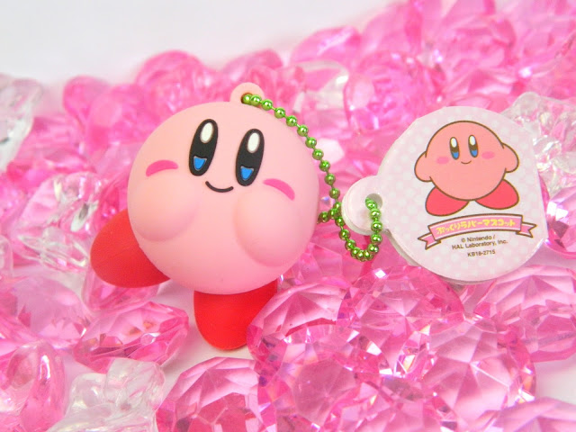 A photo of a Nintendo Kirby keychain, surrounded by gems
