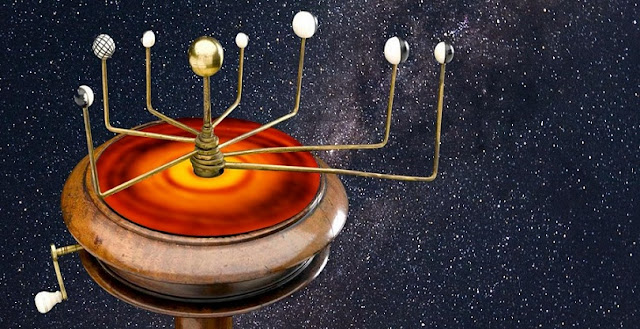 """An orrery, a type of device once used to track the movements of the planets, sitting above an infrared image of a hypothetical """"protoplanetary"""" disk that may have divided the solar system early in its history. (Credit: K. Ebert/Innovative Ideas & Methods)"""