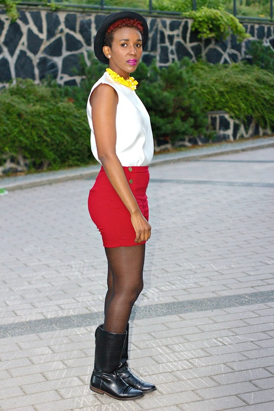woman wearing a white top paired with a pair of red shorts and black outdoor boots, she has accessorized it with a yellow neck piece and a black hat.