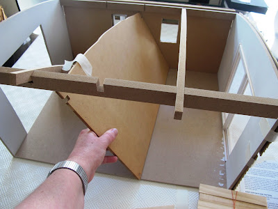 Close up of the Inside of a half-built dolls' house shed,with a hand holding a central wall at an angle because it doesn't fit where it should go.