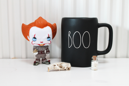 on a white surface with a white background, a Pennywise pop vinyl is next to a black hot drink mug that reads 'boo' in white font. In the foreground is a rat skull and a tiny jar of mouse bones.