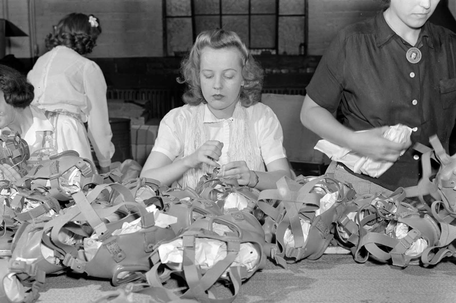 Gas mask production. Lacing head harnesses of gas masks after they have passed through all the stages of assembly and made ready for packaging, is the job of this young woman who works in the Eureka Vacuum factory which has been converted to war production.