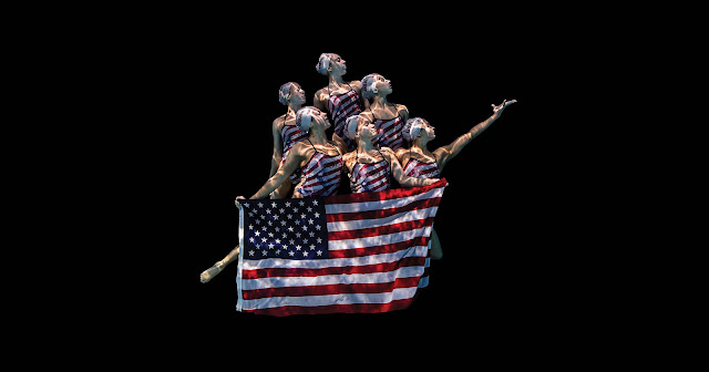 A group of synchronized swimmers underwater holding the American Flag.