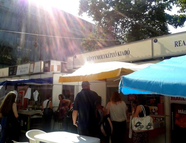 Budapest, Vörösmarty tér, 89. Ünnepi Könyvhét, 2018. június 9., Könyvmolyképző Kiadó standja, kék és sárga napernyő, napsütés, tükröződő napsugarak.