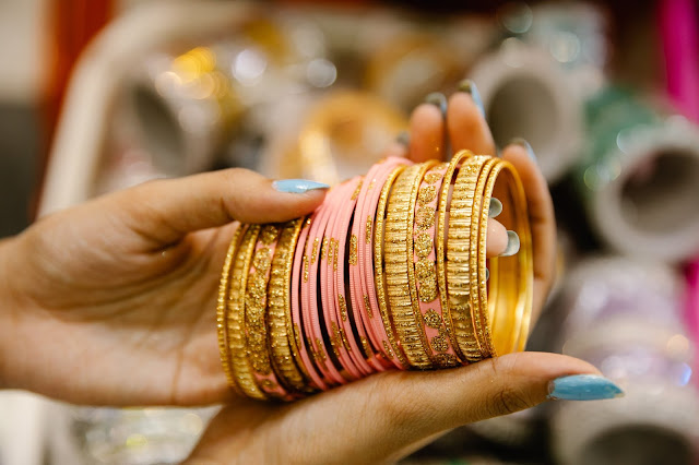 Close up of a person's hands while inspecting gold and pink bangles.