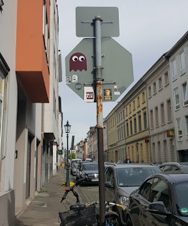 Pac-Man ghost sticker street art by Pdot in Düsseldorf, Germany