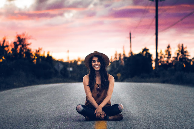 woman with hat sitting in road during sunset