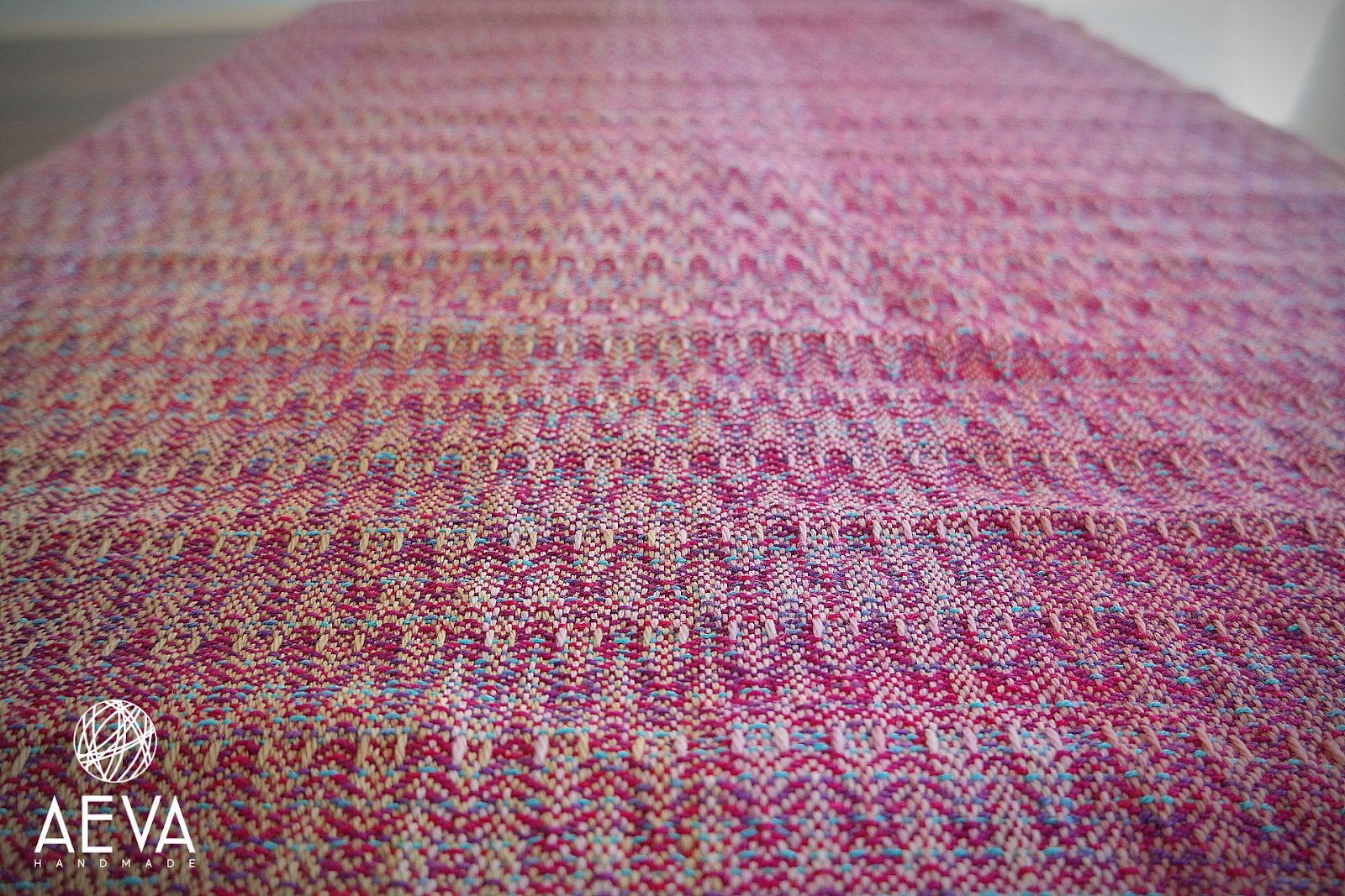 A close-up shot of the wrap lying flat on a table. The texture is highly visible, and creates a chevron effect. The mostly pink wrap takes up the whole image, and there are pops of different colours including purple, turquoise, and yellow