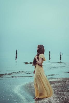 Mujer con vestido de novia teñido en amarillo en la orilla del mar