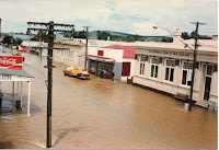 a colour photograph of brown waters flooding Otautau's Main St 1984