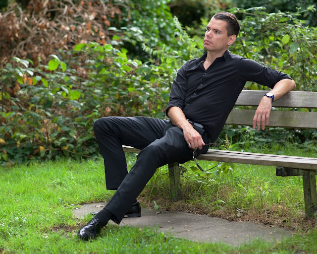 shirt and trousers seated on a bench