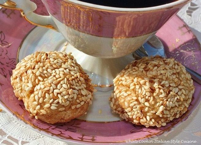 these are a lemon tasting cookie rolled into sesame seeds on a pink round demitasse plate