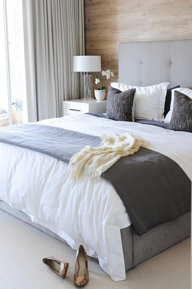 dormitorio con cabecero en madera y tonos grises