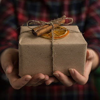 Christmas gift wrapped in brown paper & tied with string