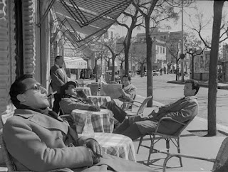 Sordi (in the foreground) lounges outside a cafe in I vitelloni