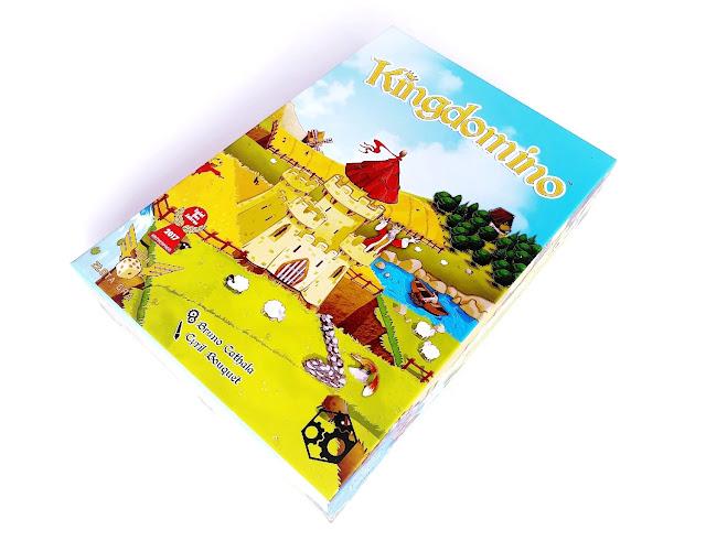 na zdjęciu pudełko gry kingdomino, na opakowaniu mamy rysunek zamku otoczonego przez pola,łąki i lasy