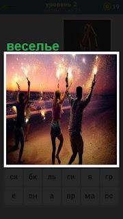 происходит веселье на берегу с огнями в руках у подростков