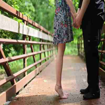 two lovers kissing on a bridge