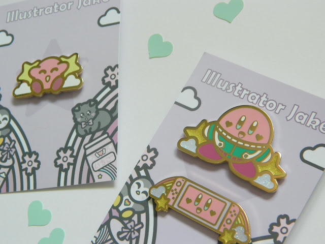 A photo showing three enamel pins by artist Illustrator Jake. They are all of Nintendo's Kirby