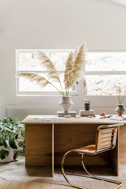 office with wood desk and leather chair, vase with pampas grass stems