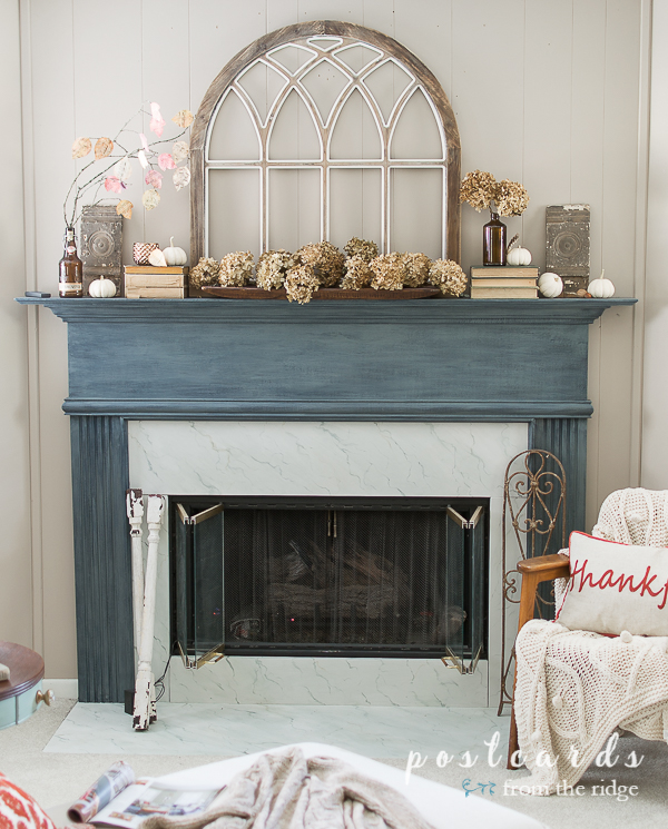 blue-gray painted fireplace mantel with vintage and natural decor items