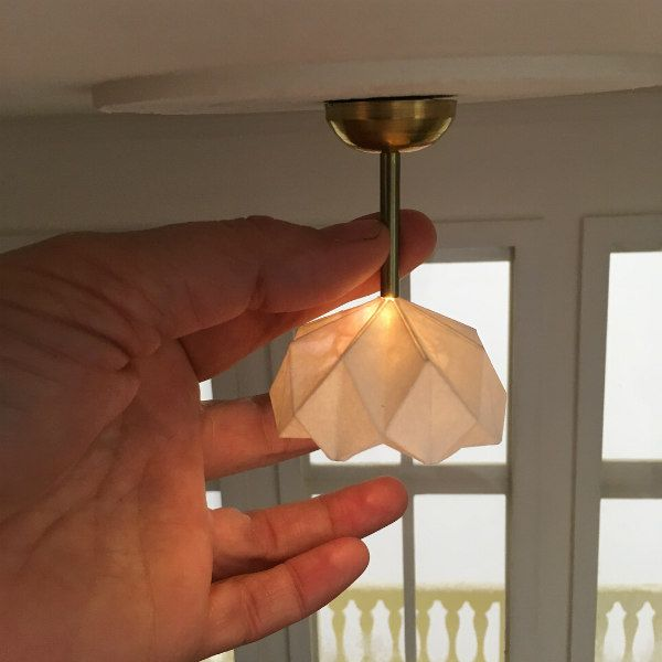 miniature folded paper ceiling light with hand to show size comparison