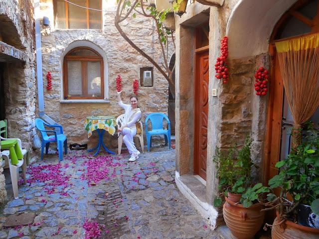 sznury pomidorów, dzbany z kwiatami, platikowe krzesła, kamienice Mesta Chios Grecja