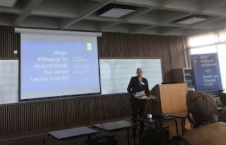"""Linda standing next to a lectern in a classroom, with her paper title """"When #TimesUp for Musical Gods: The James Levine Scandal"""" projected on a screen behind her."""