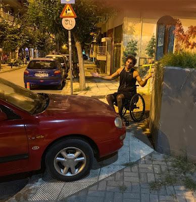 """Περιγραφή: ένα κόκκινο αμάξι, παρκαρισμένο κάθετα στο πεζοδρόμιο, αφήνει ελάχιστο χώρο. Μπροστά στο μικρό κενό ένα παλληκάρι με αμαξίδιο σηκώνει τα χέρια σε μια χειρονομία που σημαίνει """"έλεος!"""""""