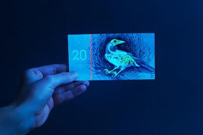 Detalhe da nota que usa tinta sensível a luz. Mostra o esqueleto do corvo que existe na nota de 20.