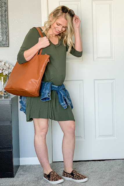 Green dress styled for spring with a denim jacket and leopard slip-on shoes