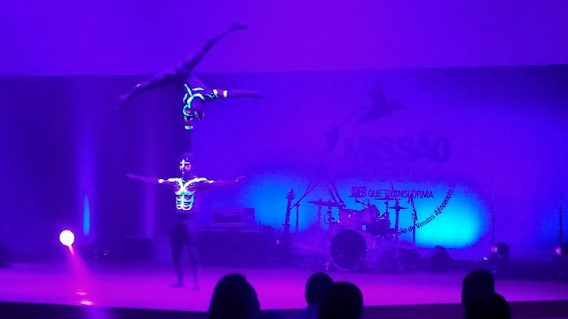 Acrobatas com pintura corporal fluorescente para show abertura convenção.