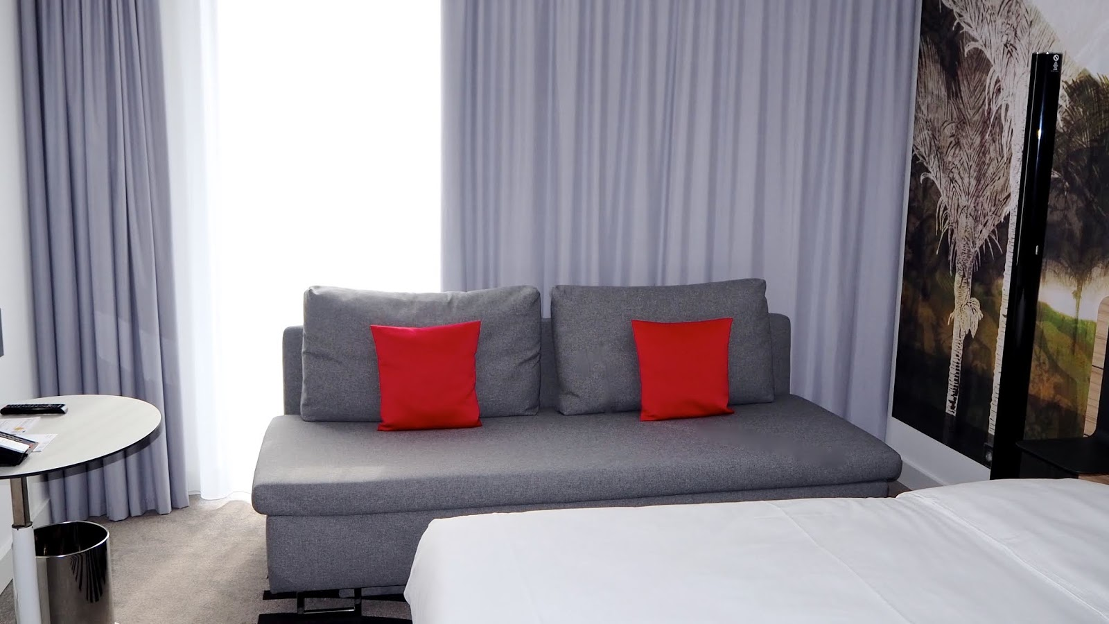 grey couch with red pillows