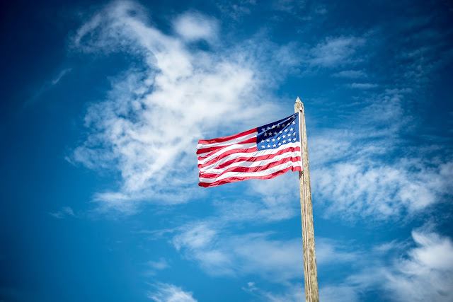 photo of U.S. flag with  photo credit by :: https://unsplash.com/@benwhitephotography