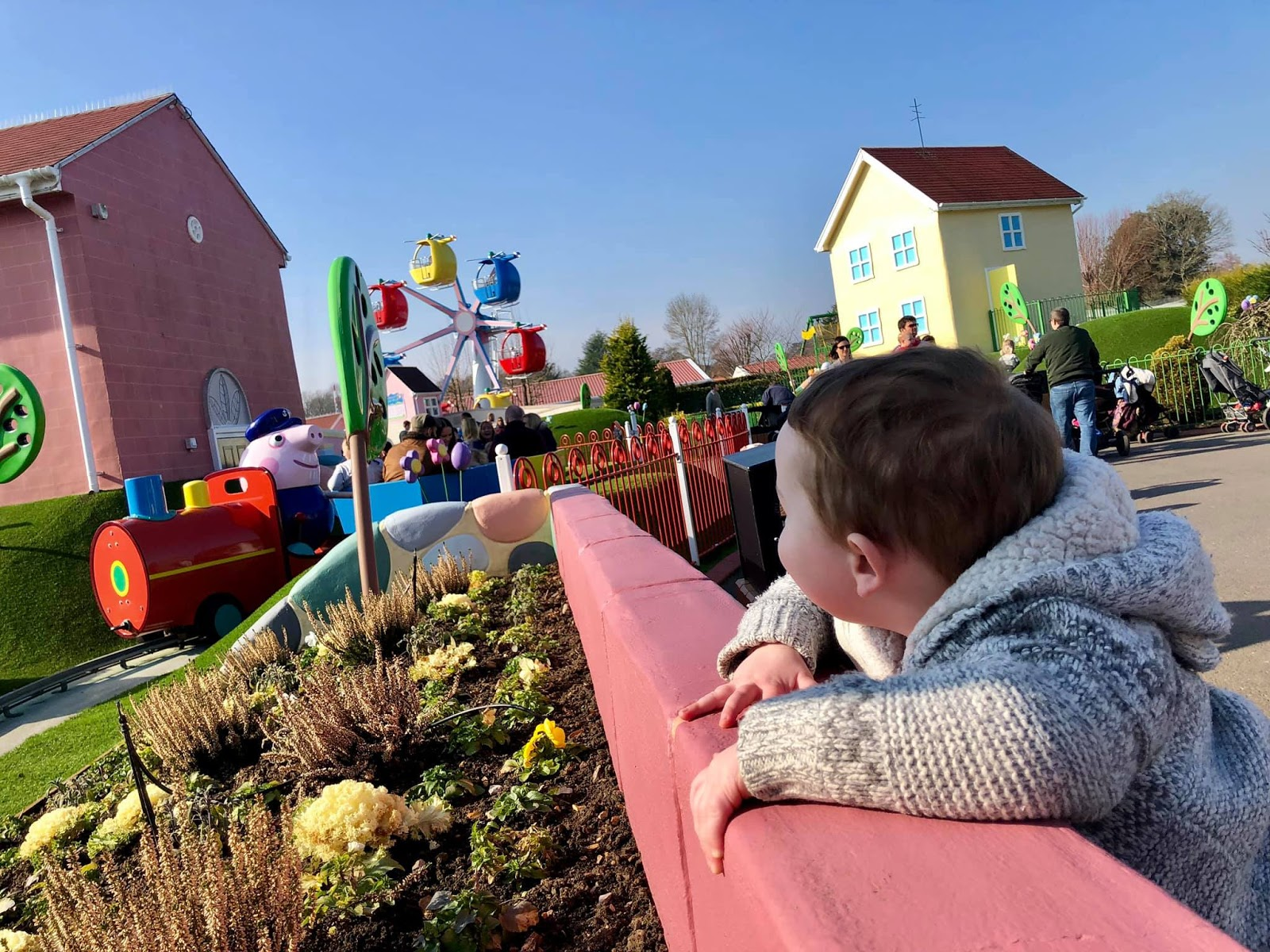 toddler watching train ride on a sunny day at peppa pig world paultons park
