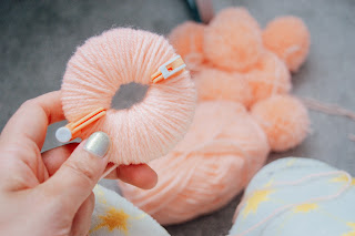 Wool wrapped around a pom-pom maker